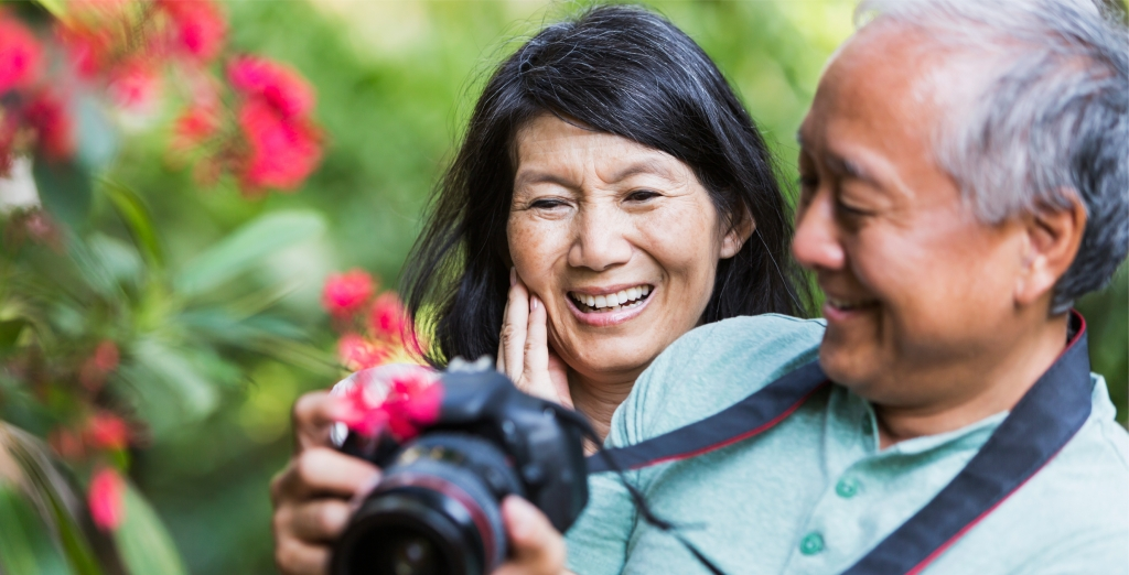 Retiring Benefits: Happy Asian couple outside looking at a picture on camera.