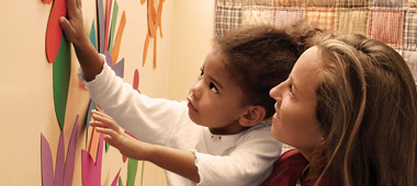 Children's Campus at Georgia Tech: Person helping child stick colorful paper to wall.
