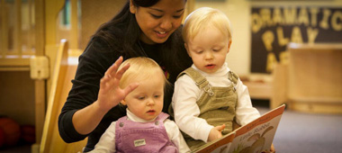 R. Kirk Landon Learning Center - adult reading to two toddlers who are sitting in front of them.